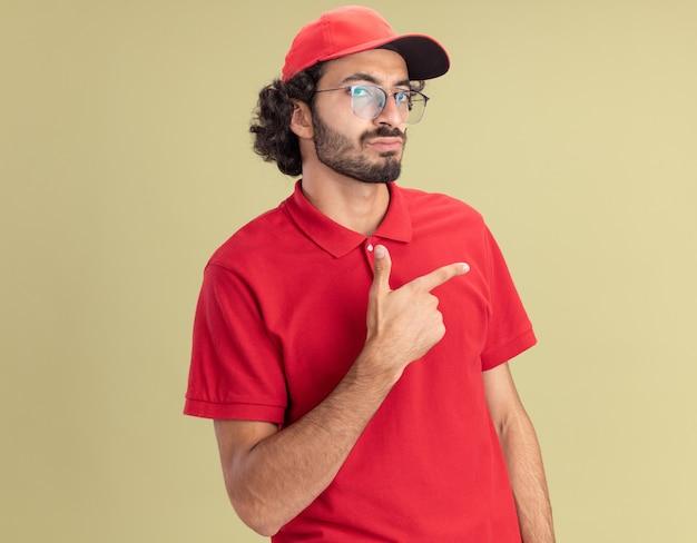 Selbstbewusster junger kaukasischer lieferbote in roter uniform und mütze mit brille, die auf die seite zeigt