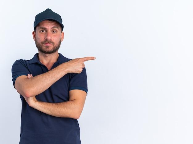 Selbstbewusster junger kaukasischer liefermann in blauer uniform und mütze, der mit geschlossener haltung in die kamera schaut, die auf die seite zeigt, die auf weißer wand mit kopienraum isoliert ist