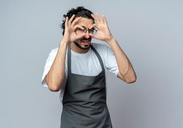 Selbstbewusster junger kaukasischer männlicher friseur mit brille und welligem haarband in uniform, der eine blickgeste zwinkert und zunge zeigt