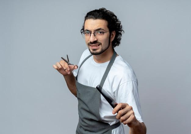 Selbstbewusster junger kaukasischer männlicher friseur mit brille und welligem haarband in uniform, der in der profilansicht steht, eine schere hält und den kamm ausstreckt
