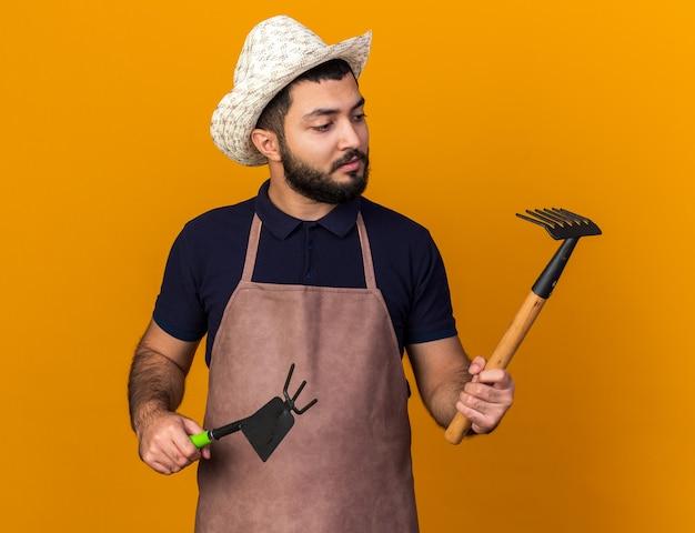 Selbstbewusster junger kaukasischer männlicher gärtner, der gartenhut hält, der hacke-harken hält und harken lokalisiert auf orange wand mit kopienraum betrachtet