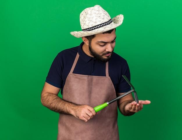 Selbstbewusster junger kaukasischer männlicher gärtner, der gartenhut hält hält und hacke rechen lokalisiert auf grüner wand mit kopienraum betrachtet
