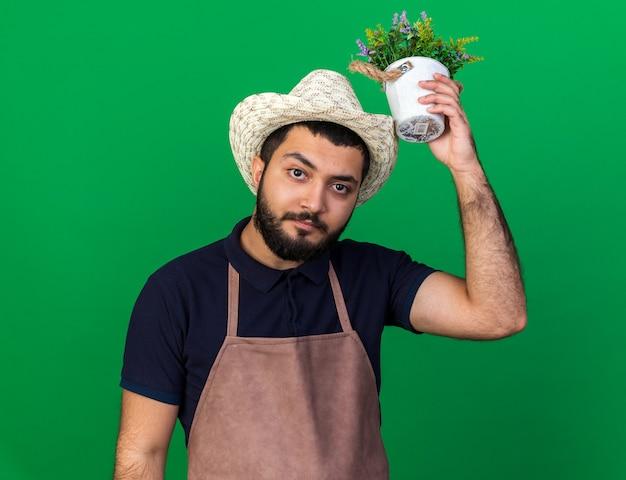 Selbstbewusster junger kaukasischer männlicher gärtner mit gartenhut, der blumentopf über dem kopf hält, isoliert auf grüner wand mit kopierraum