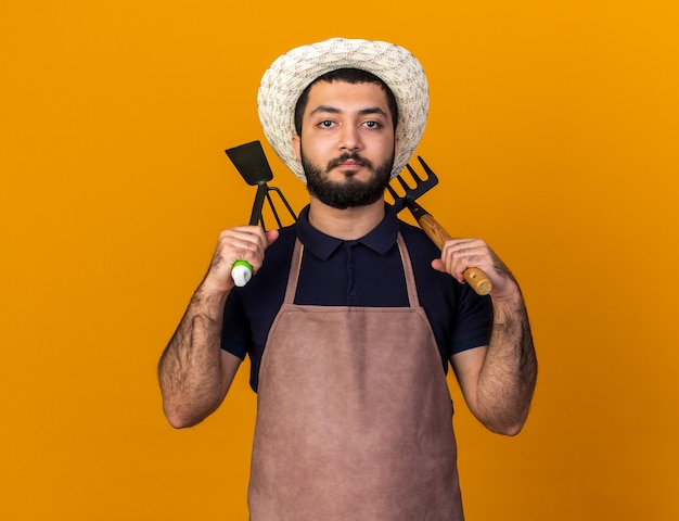 Selbstbewusster junger kaukasischer männlicher gärtner mit gartenhut, der rechen und hacke auf den schultern hält, isoliert auf oranger wand mit kopierraum