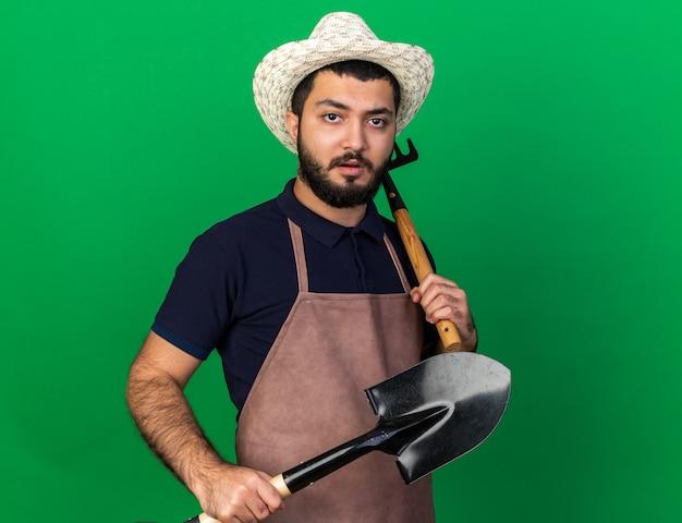 Selbstbewusster junger kaukasischer männlicher gärtner mit gartenhut mit rechen und spaten isoliert auf grüner wand mit kopierraum with