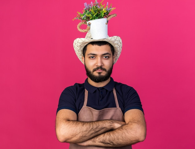 Selbstbewusster junger kaukasischer männlicher gärtner mit gartenhut steht mit verschränkten armen, der blumentopf auf dem kopf hält, isoliert auf rosa wand mit kopierraum