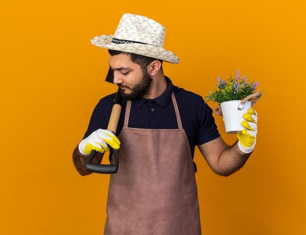 Selbstbewusster junger kaukasischer männlicher gärtner mit gartenhut und handschuhen, der blumentopf und spaten auf der schulter hält, isoliert auf oranger wand mit kopierraum