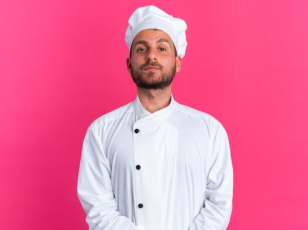 Selbstbewusster junger kaukasischer männlicher koch in kochuniform und mütze, der die hände zusammenhält und die kamera isoliert auf rosa wand betrachtet