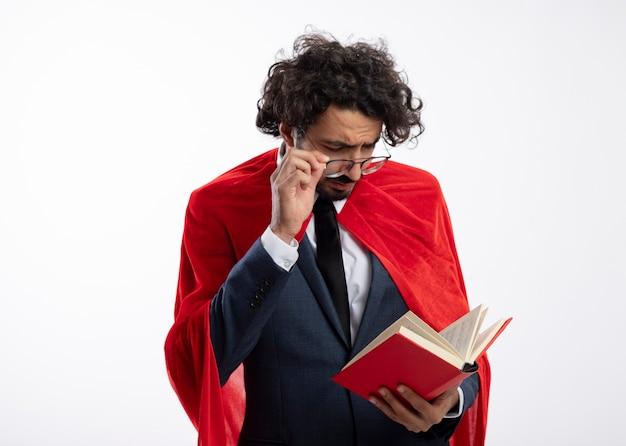 Selbstbewusster junger kaukasischer superheldenmann, der anzug mit rotem umhang trägt und das buch durch eine optische brille betrachtet
