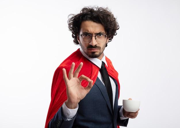 Selbstbewusster junger kaukasischer superheldenmann in optischer brille, der anzug mit rotem mantel trägt, gestikuliert ok handzeichen und hält tasse