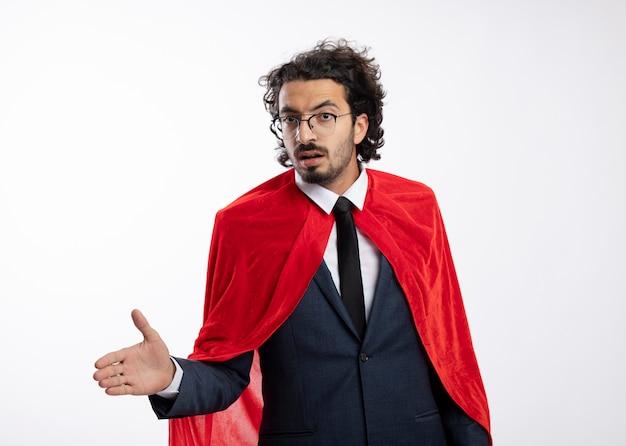 Selbstbewusster junger kaukasischer superheldenmann in optischer brille, der anzug mit rotem mantel trägt, hält die hand mit blick auf die kamera aus