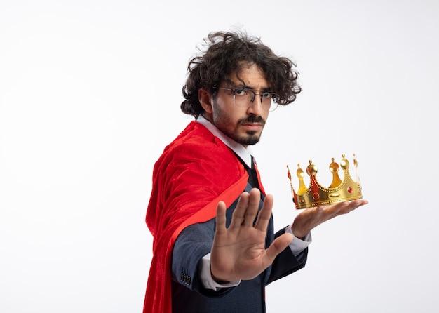 Selbstbewusster junger kaukasischer superheldenmann in optischer brille, der anzug mit rotem mantel trägt, hält krone und gesten stopphandzeichen