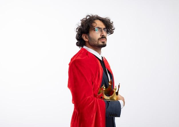 Selbstbewusster junger kaukasischer superheldenmann in optischer brille, der anzug mit rotem mantel trägt, steht seitlich mit krone holding