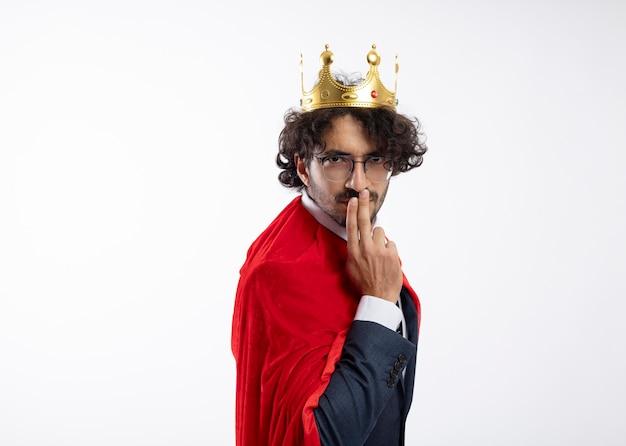 Selbstbewusster junger kaukasischer superheldenmann in optischer brille, der anzug mit rotem mantel und krone trägt, steht seitlich und legt die finger auf den mund
