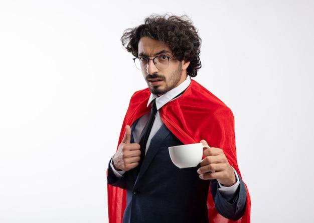 Selbstbewusster junger kaukasischer superheldenmann in optischer brille, der anzug mit rotem umhang trägt, daumen hoch und hält tasse holds
