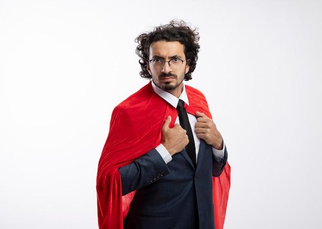 Selbstbewusster junger kaukasischer superheldenmann in optischer brille, der anzug mit rotem umhang trägt, hält umhang