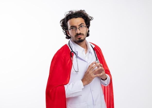 Selbstbewusster junger kaukasischer superheldenmann in optischer brille, der eine arztuniform mit rotem umhang trägt und mit stethoskop um den hals die hände zusammenhält