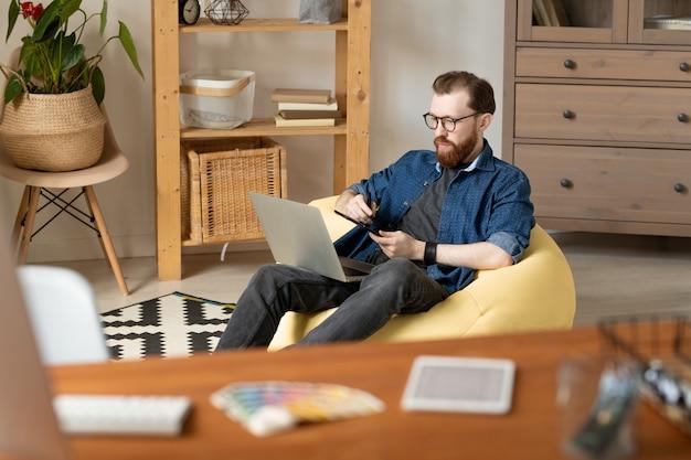 Selbstbewusster junger layouter mit bart, der im gelben sitzsack sitzt und digitalisierertablett verwendet, während von zu hause aus arbeitend