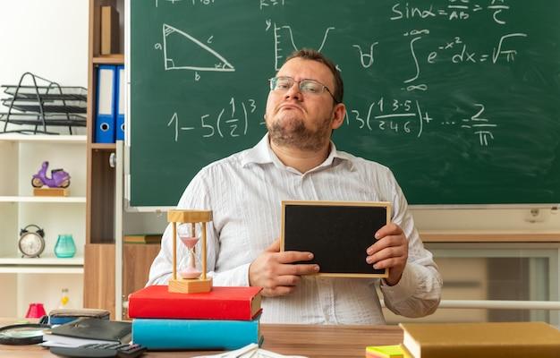 Selbstbewusster junger lehrer mit brille, der am schreibtisch mit schulmaterial im klassenzimmer sitzt und eine mini-tafel zeigt, die nach vorne schaut