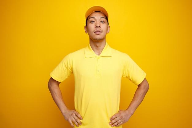 Selbstbewusster junger lieferbote, der mütze und uniform trägt und hände auf taille hält