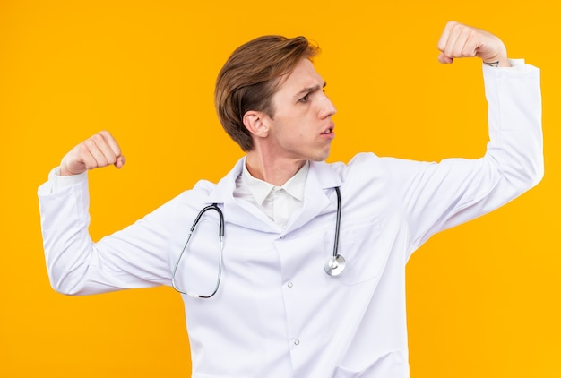 Selbstbewusster junger männlicher arzt, der ein medizinisches gewand mit stethoskop trägt und eine starke geste zeigt