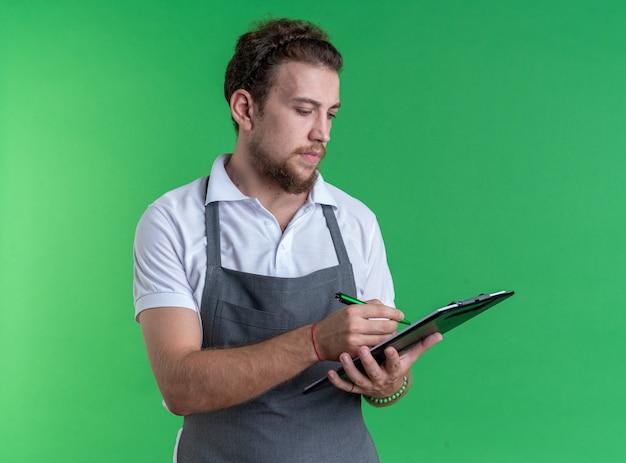 Selbstbewusster junger männlicher barbier, der eine uniform trägt, die zwischenablage hält und etwas isoliert auf die grüne wand schreibt?