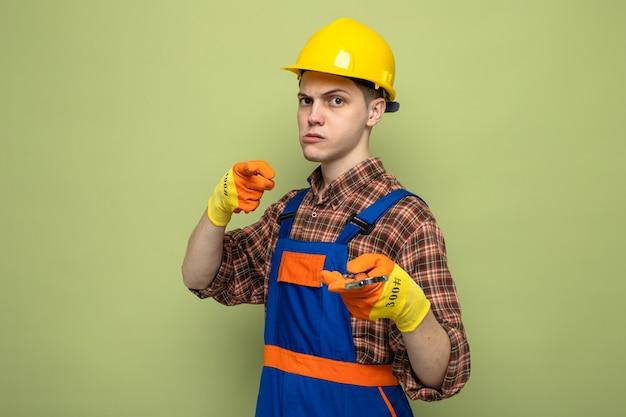 Selbstbewusster junger männlicher baumeister, der uniform mit handschuhen trägt, die einen gabelschlüssel halten