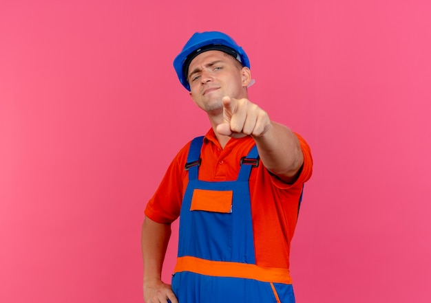 Selbstbewusster junger männlicher baumeister, der uniform und schutzhelm trägt, der sie geste zeigt