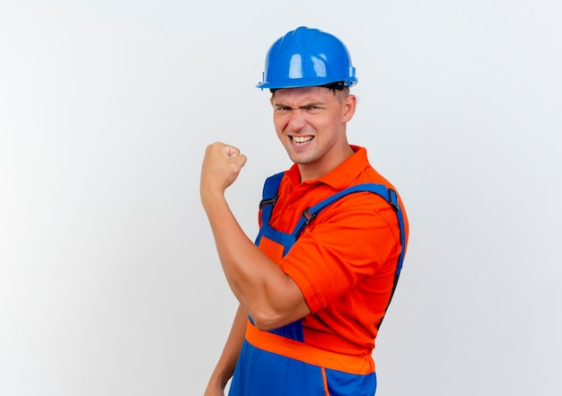 Selbstbewusster junger männlicher baumeister, der uniform und schutzhelm trägt und starke geste tut