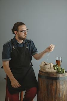 Selbstbewusster junger männlicher brauer mit selbst hergestelltem bier im glas auf holzfass auf grau