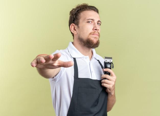 Selbstbewusster junger männlicher friseur in uniform, der haarschneidemaschinen hält und die hand isoliert auf olivgrüner wand ausstreckt