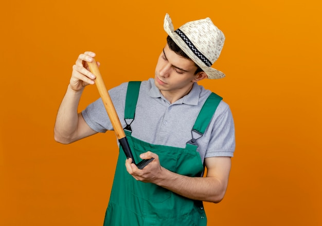 Selbstbewusster junger männlicher gärtner, der gartenhut trägt, schaut und hält rechen kopfüber