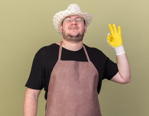 Selbstbewusster junger männlicher gärtner mit gartenhut und handschuhen, der eine gute geste zeigt, die auf olivgrüner wand isoliert ist?