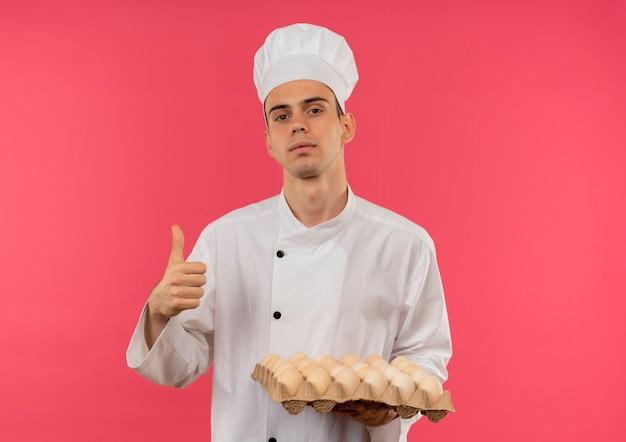 Selbstbewusster junger männlicher koch, der kochuniform trägt, hält charge von eiern seinen daumen oben auf isolierter rosa wand