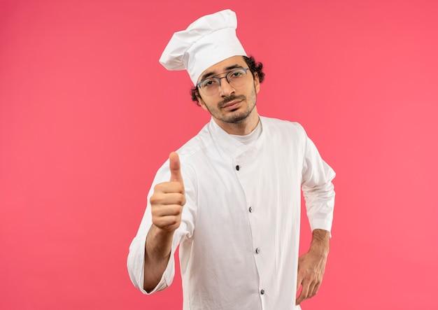 Selbstbewusster junger männlicher koch, der kochuniform und brille trägt, die hand auf hüfte und daumen hoch legt