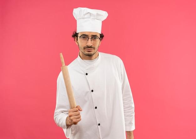 Selbstbewusster junger männlicher koch, der kochuniform und gläser hält, die nudelholz halten