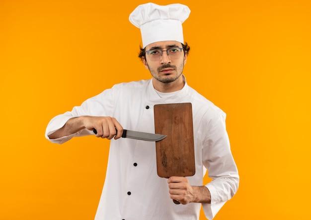 Selbstbewusster junger männlicher koch, der kochuniform und gläser hält, die schneidebrett und messer halten