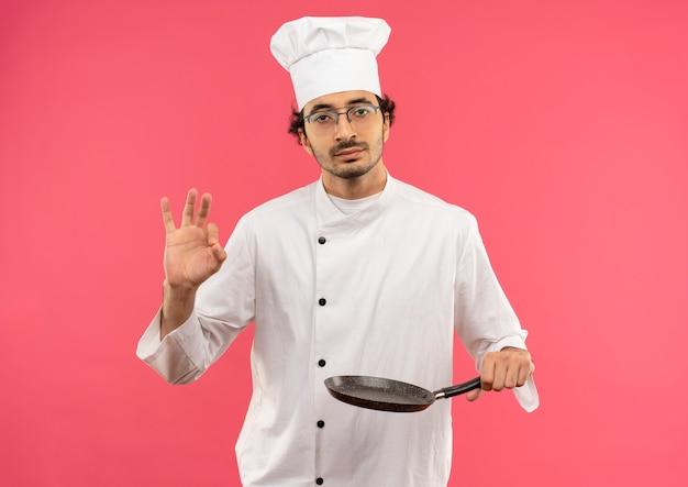 Selbstbewusster junger männlicher koch, der kochuniform und gläser trägt, die bratpfanne halten und okey geste zeigen