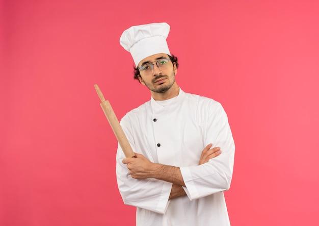 Selbstbewusster junger männlicher koch, der kochuniform und gläser trägt, die hände kreuzen und nudelholz halten