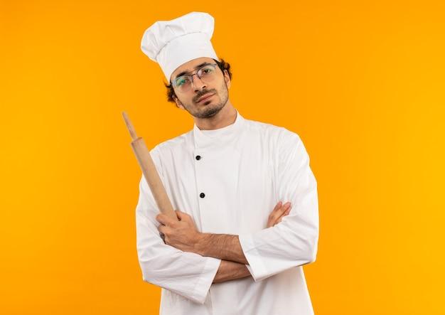 Selbstbewusster junger männlicher koch, der kochuniform und gläser trägt, die nudelholz halten und hände kreuzen
