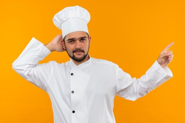 Selbstbewusster junger männlicher koch in kochuniform, der die hand hinter den kopf legt und auf die seite zeigt, isoliert auf oranger wand