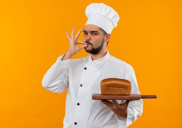 Selbstbewusster junger männlicher koch in kochuniform, der ein schneidebrett mit brot darauf hält und eine leckere geste einzeln auf der orangefarbenen wand macht