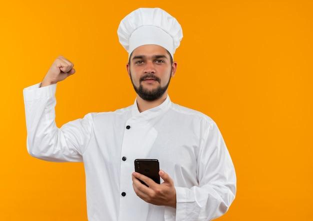 Selbstbewusster junger männlicher koch in kochuniform, der handy hält und stark isoliert auf oranger wand mit kopienraum gestikuliert