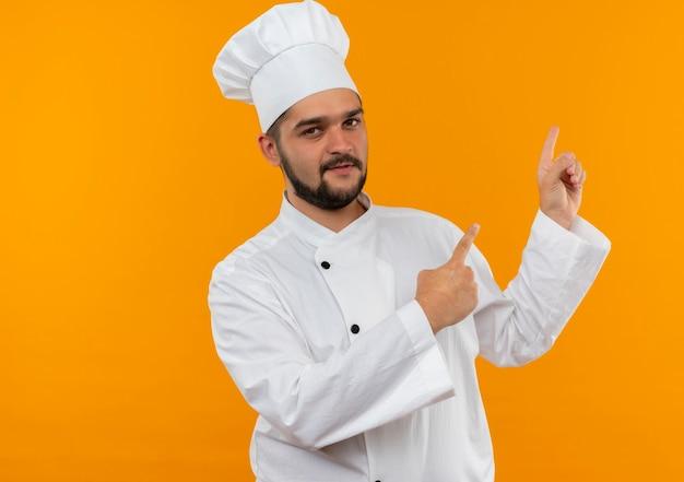 Selbstbewusster junger männlicher koch in kochuniform, der isoliert auf orangefarbener wand mit kopierraum nach oben zeigt