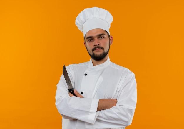 Selbstbewusster junger männlicher koch in kochuniform, der mit geschlossener haltung steht und das messer isoliert auf oranger wand mit kopierraum hält
