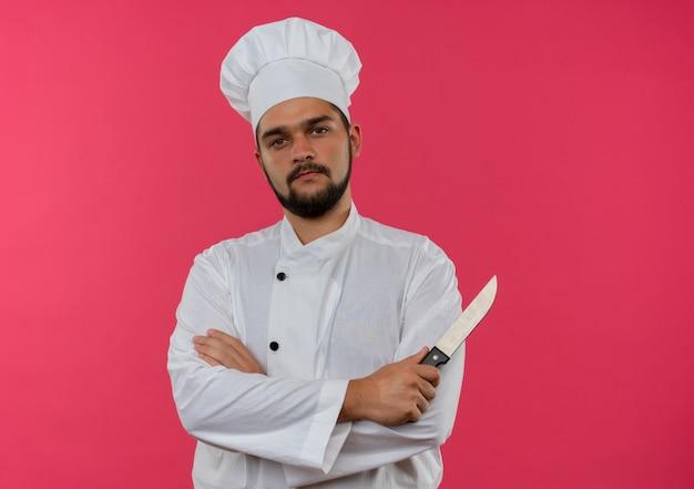 Selbstbewusster junger männlicher koch in kochuniform, der mit geschlossener haltung steht und messer isoliert auf rosa wand hält