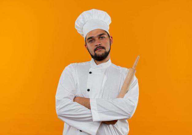 Selbstbewusster junger männlicher koch in kochuniform, der mit geschlossener haltung steht und nudelholz isoliert auf oranger wand mit kopierraum hält