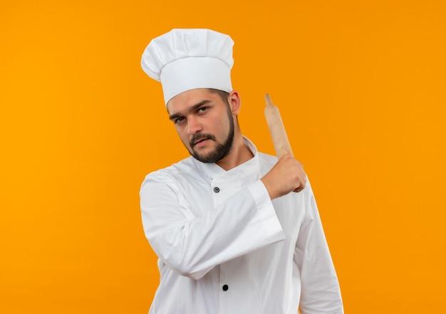 Selbstbewusster junger männlicher koch in kochuniform, der nach hinten mit nudelholz zeigt, isoliert auf oranger wand mit kopierraum