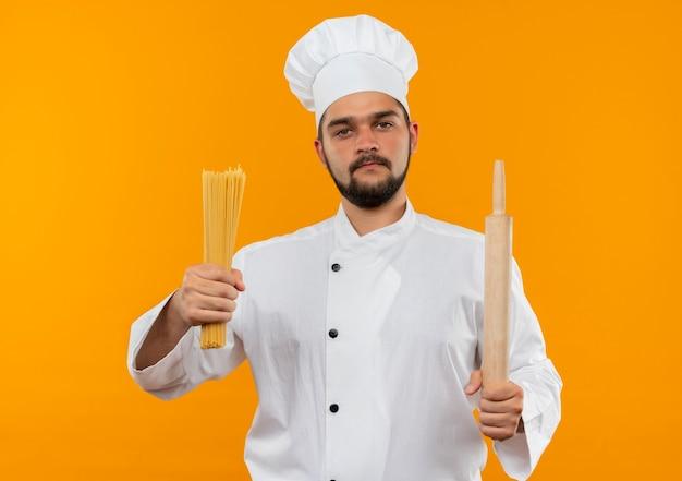 Selbstbewusster junger männlicher koch in kochuniform mit spaghetti-nudeln und nudelholz isoliert auf oranger wand
