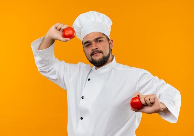 Selbstbewusster junger männlicher koch in kochuniform mit tomaten isoliert auf oranger wand
